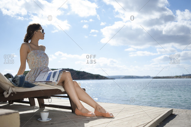Side view of woman sitting on lounge chair in Mallorca, Spain