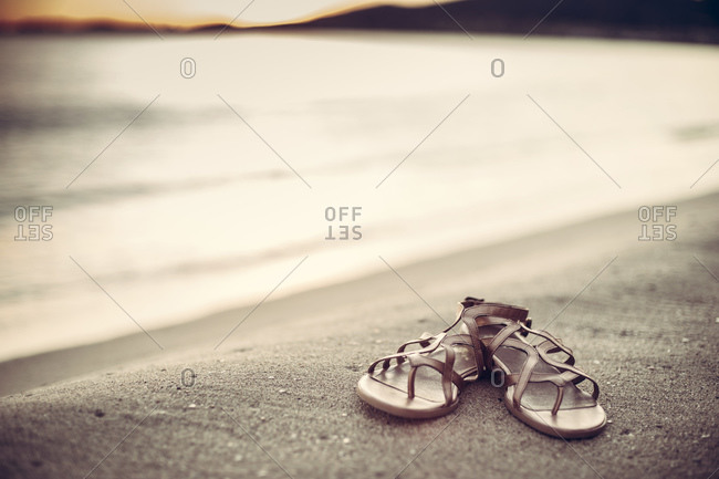 Pair of sandals on a sandy beach