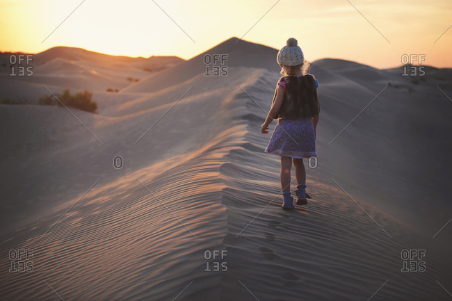 Young girl walking on a sand dune at sundown