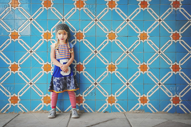 Portrait of a young girl leaning against a wall