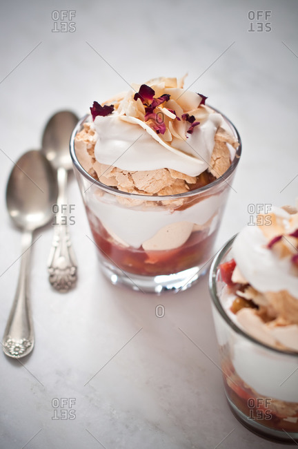 Two portions of a creamy dessert of coconut, crumbly meringue and rhubarb with rose petals