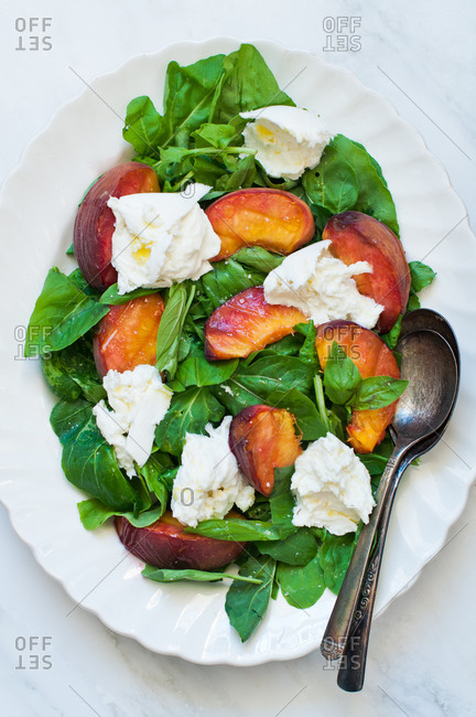 Top view of summer salad of grilled peaches, buffalo mozzarella and baby spinach