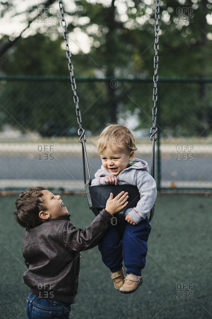 Little boy pushing baby brother on swing