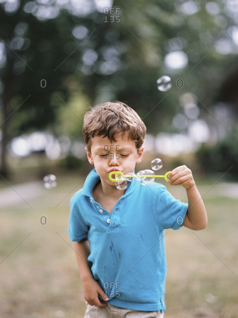 Little boy blowing bubbles outside