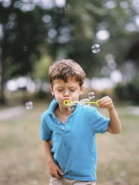 Little boy blowing bubbles outside