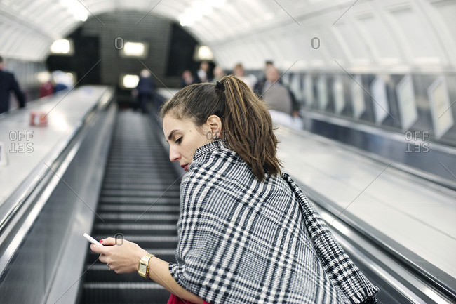 Young woman looking at her smartphone on an escalator