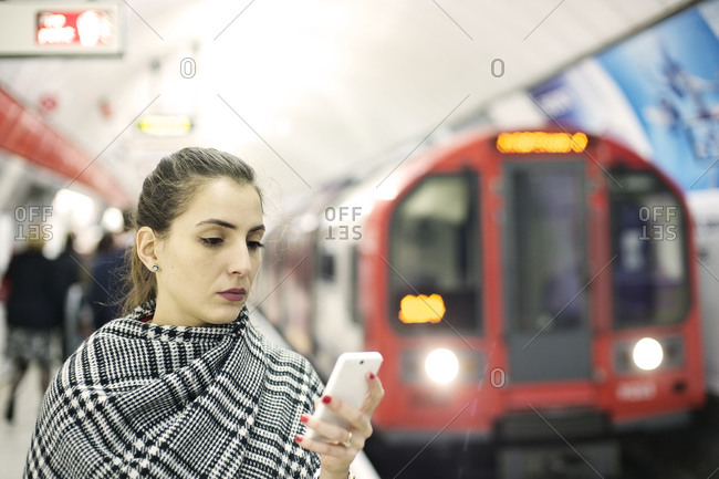 Businesswoman using smartphone on a subway station