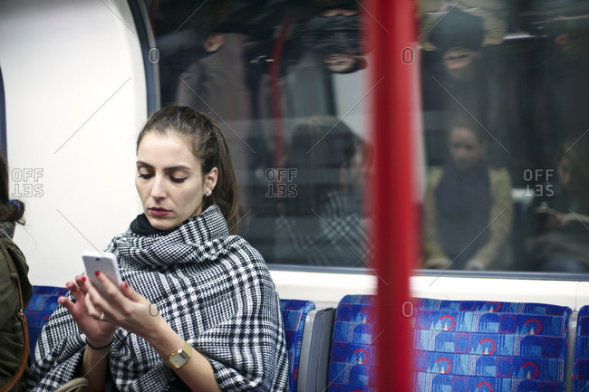 Businesswoman looking at her smartphone on a train