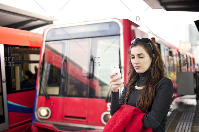 Businesswoman looking at her smartphone on platform