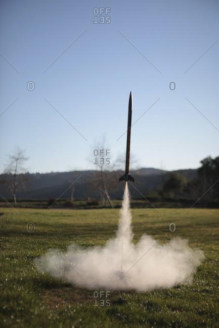 A toy rocket launching in backyard