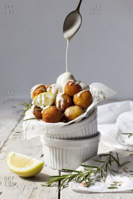 Balls of fried potatoes with lemon, rosemary and yogurt sauce