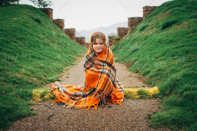 Child with plaid blanket in front of  old foundation