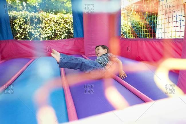 Boy falling midair in bouncy castle