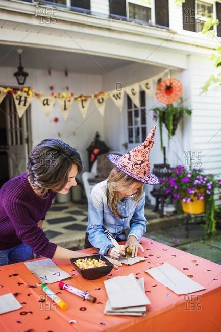 Young girl decorating treat bags with her mother on Halloween