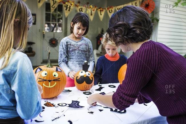 Children decorating pumpkins with their mother