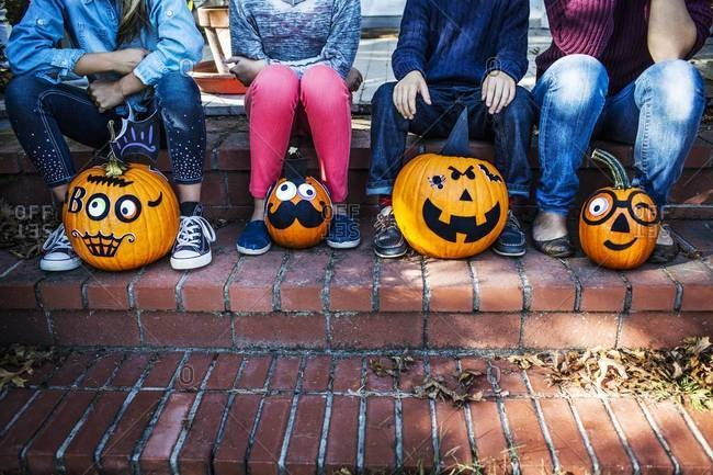 Children sitting on a porch with decorated pumpkins on Halloween