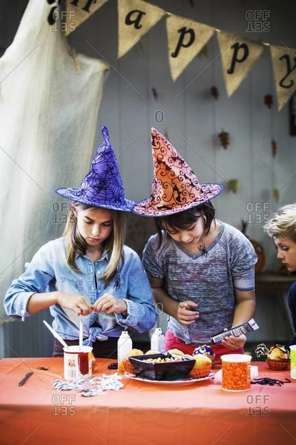 Young girls preparing Halloween cupcakes