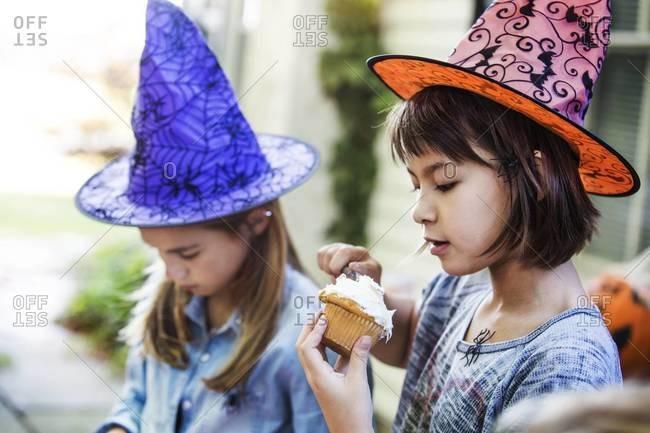 Young girl eating a cupcake on Halloween
