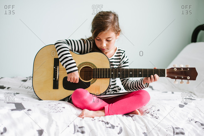 Young girl playing the guitar on her bed