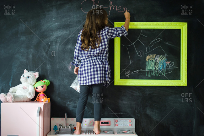 Back view of a girl standing on a toy kitchen and drawing on blackboard