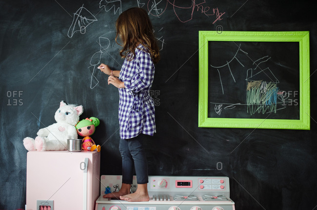 Side view of a girl standing on a toy kitchen and drawing on blackboard