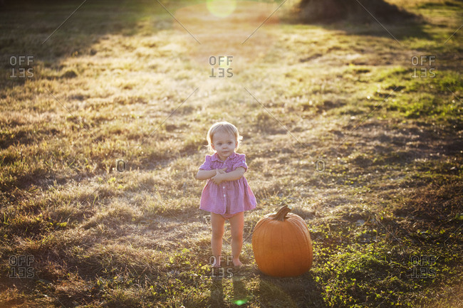 Young girl standing next to a huge pumpkin