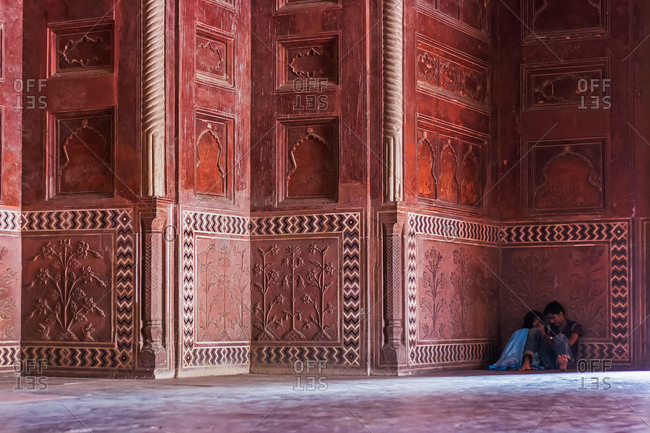 Agra, India - November 15, 2008: Couple sitting in a corner of the Taj Mahal