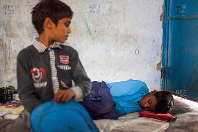 Bettiah, Bihar, India - November 15, 2012: Young boy sleeping in a government school