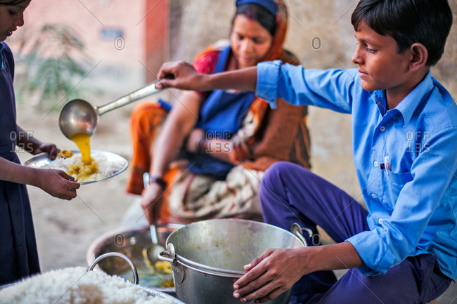Bettiah, Bihar, India - November 15, 2012: Young boy serving food in a government school