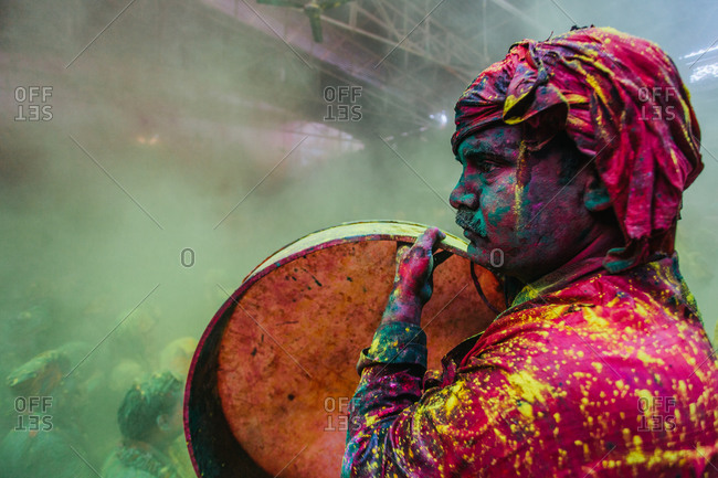 Drummer drenched in colors performing the ritual of Samaaj in Barsana, India