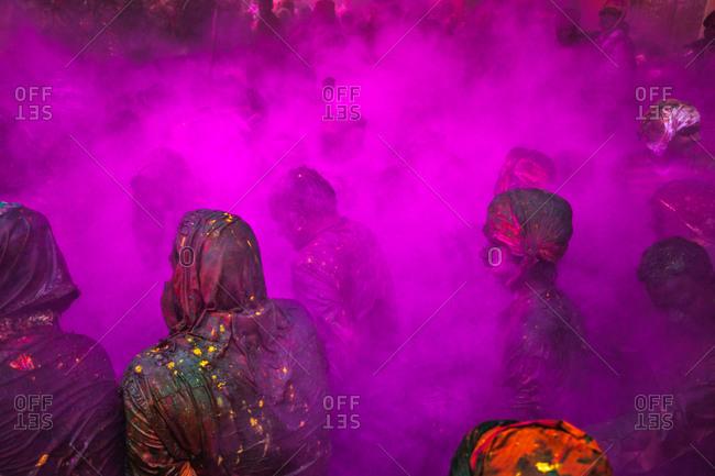 Mathura, Uttar Pradesh, India - February 23, 2010: People covered with cyclamen powder paint at the Braj Holi festival in Uttar Pradesh