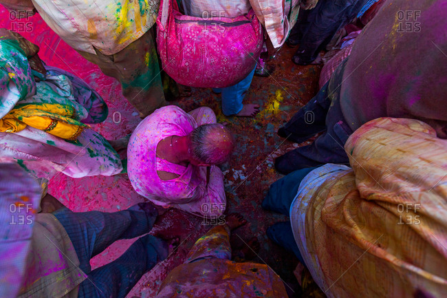 Man squatting in the crowd at the festival of Nandgaon Holi in Mathura, India