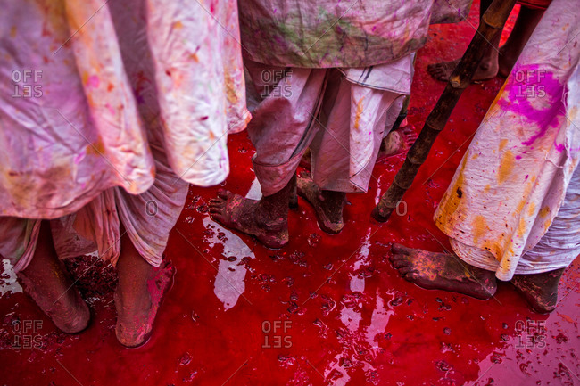 Men standing in red paint puddle at the festival of Nandgaon Holi in Mathura, India