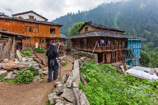 Hiker passing through Nakthan village in Himachal Pradesh, India