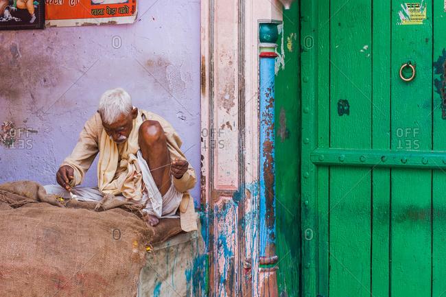 Mathura, Uttar Pradesh, India - February 12, 2009: Senior Hindu man sewing outdoor in Dauji
