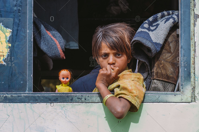 Mathura, Uttar Pradesh, India - February 12, 2009: Portrait of an Indian kid leaning to the window