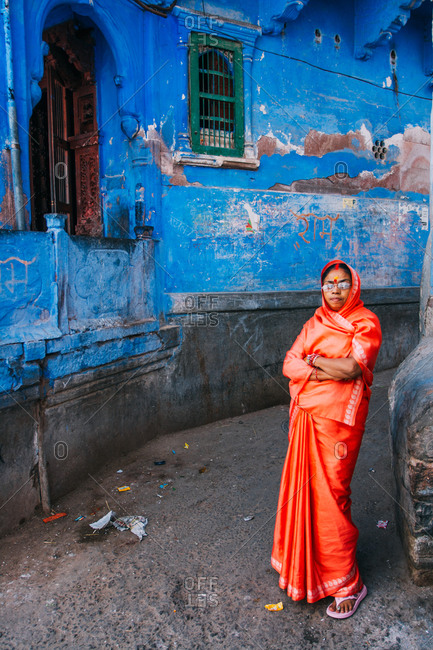 City of Jodhpur, Rajasthan - India - February 2, 2009: Portrait of a Rajasthani lady wearing bright orange Saree in the blue streets of Jodhpur