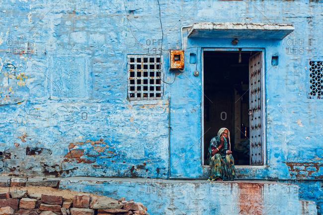 City of Jodhpur, Rajasthan - India - February 4, 2009: An old lady sits on the door of her house in Jodhpur