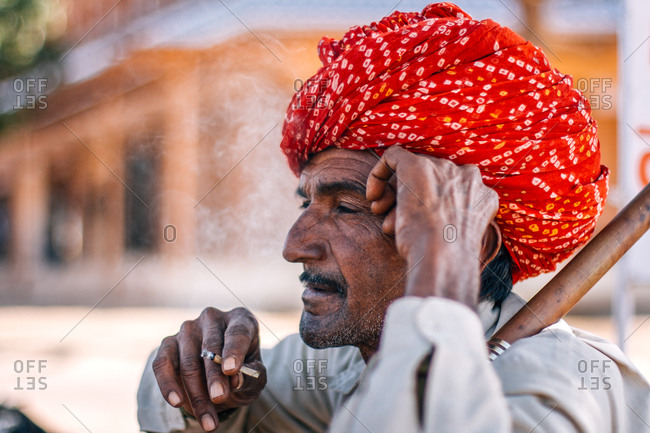 Osian, City of Jodhpur, Rajasthan - India - February 3, 2009: Portrait of Rajasthani man wearing a red turban smoking