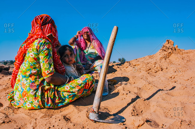 Osian, City of Jodhpur, Rajasthan - India - February 3, 2009: Rajasthani women resting with their kid after work in the desert