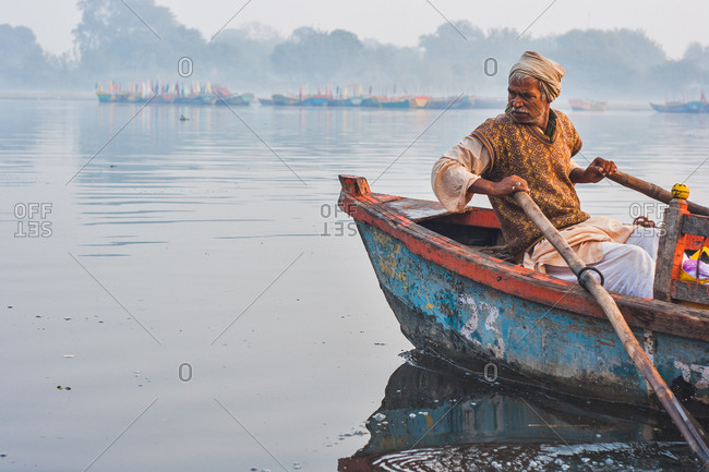 Mathura Uttar Pradesh, India - November 11, 2008: Indian man rowing boat on river