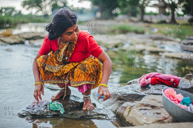 Sewagram, Wardha, Maharasthra, India - October 1, 2012: Woman washing clothes in river at a small town of Sewagram