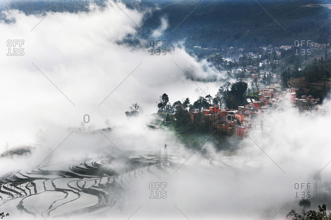 Clouds rolling into a village on a terraced hillside, China