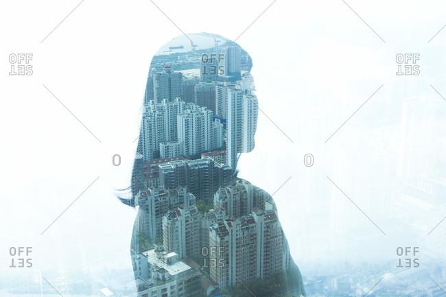 City below seen through silhouette reflection in window