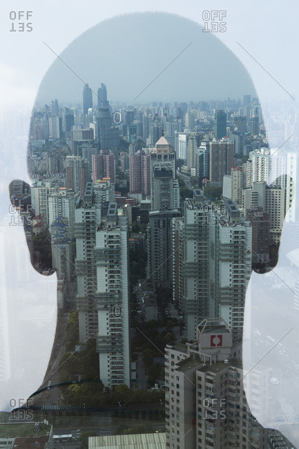City below seen through reflection of man's silhouetted head