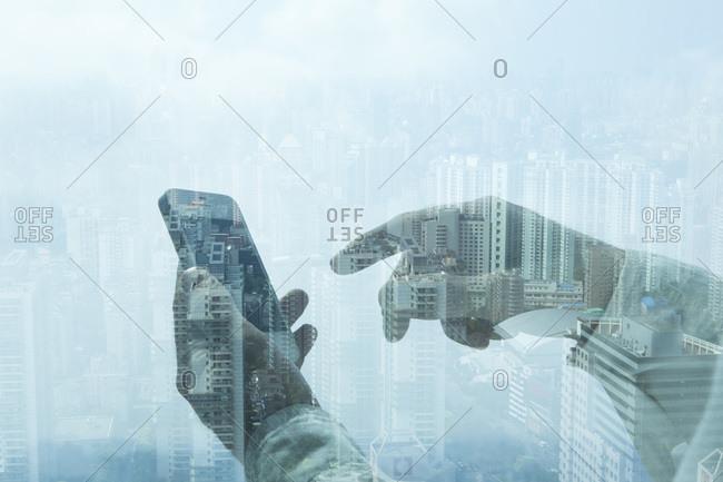 City below seen through reflection of hands using smart phone