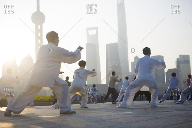 People doing tai chi in the morning as the sun rises through the towers of Pudong, Shanghai