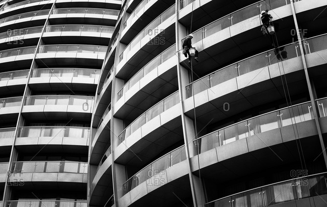 Two men cleaning the facade of a building