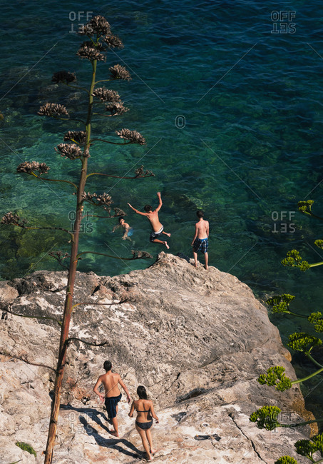 People jumping off the cliff into the sea in Croatia
