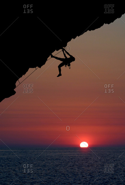 Person climbing a rock at sunset in Pelion, Greece